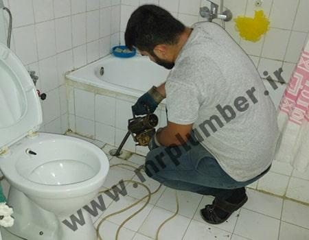 لوله بازکنی کفشور حمام با فنر برقی بدون کثیف کاری برای کفشور حمام که احتمالا با مو گرفته شده است.